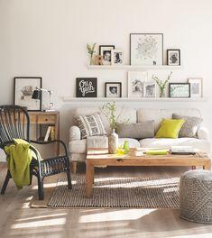 004decorar paredes. salón con sofá blanco y mesa de centro de madera y pared decorada con marcos de fotos