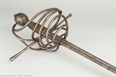 """Museo Arqueológico Nacional Espada de acero tipo """"de lazo"""" con guarnición simple de lazo mediante dos placas caladas unidas por gavilanes rectos y cilíndricos que se ensanchan en los extremos. Pomo esférico estirado facetado, rematado con un botón circular. La empuñadura cilíndrica, algo aplastada, está reforzada por hilos de cobre retorcido. La hoja es estrecha, de cuatro mesas, terminada en punta y acanalada en su primer tercio, donde se han grabado dos inscripciones en ambos lados de la…"""