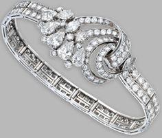 Platinum and Diamond Bracelet, Mellerio, Paris. The articulated strap centered by an openwork plaque of scroll design, set throughout with pear-shaped, marquise-shaped and round diamonds weighing approximately 14.60 carats.