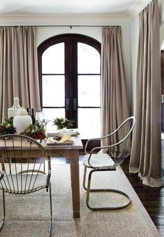 Love the thin metal of the chairs against the voluptuous softness of the drapes    great drapery + black door & trim .