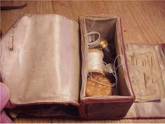 "Civil war era sewing kit, sometimes called ""Shaker kit,"" leather exterior, satin interior, box holds thimbles, needles, spools of thread, silk tie straps at one end. 4"" across"
