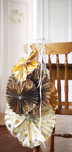 Weihnachtsschmuck gefertigt aus VINTERMYS Geschenkpapier in verschiedenen Mustern in Goldfarben an der Rückenlehne eines Holzstuhls
