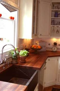 Ivory cabinets, copper farmhouse sink, butcher block countertops.