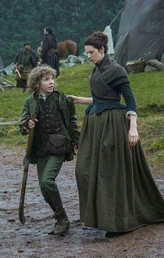 ~ Claire escorts Fergus away from the scrimmaging with other Highland soldiers.  Outlander, Season 2