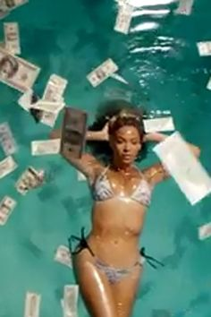 Beyonce flashed her bikini body in a pool filled with money.