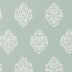 Raja Wallpaper A woodblock print style wallpaper of diamond shaped damask motifs repeated in white on a teal background.