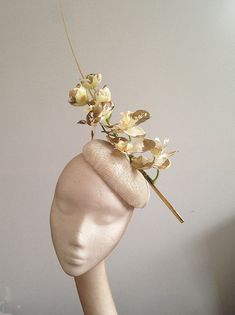 Beautiful gold edged white orchids floating up from the ivory/gold sinamay hat, the orchids lean against a long gold quill to give the hat eye