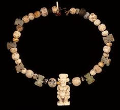 Necklace of thirty-five beads and composition pendants. Central pendant of Bes. Seven moulded pendants in green or blue faience of the head of Bes, with two pairs of suspension holes in the back; the heads are not completely identical. Twenty-six eye beads. Three oblate spherical beads of blue or dark glass appearing black. Four biconical beads, three of blue and one of yellow glass. One blue glass melon bead. One black stone biconical bead.