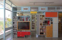 | Partition apartment | The open space is divided by a partition in the middle, creating privacy for two workspaces and a library. Made from iron and pressed wood, the partition is coloblocked with shades of blue, red and yellow. These friendly colours inform the scheme and the vibe of the apartment.