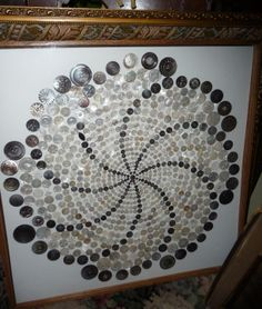 Framed assortment of Mother of Pearl Buttons in a pinwheel design.
