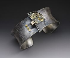 Cuff | Roger Rimel. Sterling, 14k gold, pyrite in slate, yellow sapphires, anticlastic formed, patina.