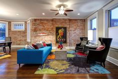 The long brick accent wall lining this living room adds warmth and rough texture to the pleasing lines in this eclectic living room. A low-back modern blue sofa is a bright contrast to the black leather armchairs with nailhead trim. The paint splatter design on the rug adds pops of color and a softening detail to the design.
