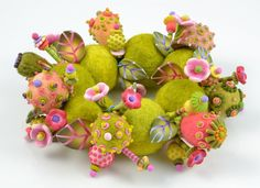 Hand dyed and hand felted merino wool beads, hand crafted polymer beads, glass seed beads, plastic coated wire. debra dew