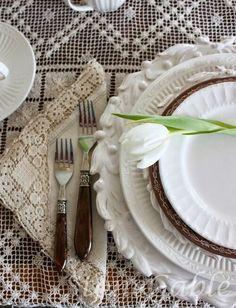 Beautiful white dishware with cream tablecloth + napkin.