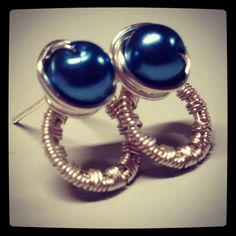 Wire wrapped post earrings with dark blue glass pearls.
