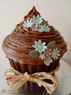 Giant Chocolate Cupcake, from vintagerosecupcakes.com. A delicious Chocolate cake base that goes all the way to the cakes topping, it's all cake! Covered in chocolate butter cream icing  and decorated with blue sugar paste flowers.