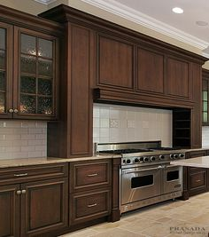 """Traditional / Classic Kitchen. Dark stained cabinetry with large flanking hood over 48"""" range. www.prasadakitchens.com"""