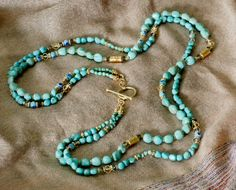 1334149N | It's 2 necklaces in one - a double-strand wraparound necklace of Mexican turquoise nuggets embellished with blue and aqua Murano glass beads, 24K vermeil, and closed with a simple vermeil toggle clasp. Can be worn as a demi-opera-length or doubled into 4-strand composition about 17 inches. Length 34 inches. Can also be wrapped around your wrist as a stunning bracelet. (Overall length can be adjusted for slight upcharge.) $475