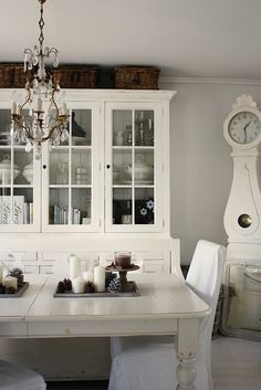Gorgeous white gustavian clock and hutch in this white dining room area.  Love the crystal chandelier. #whitediningroom #europeanfurniture
