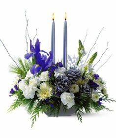 Table Star: A traditional centerpiece in that it highlights the table by featuring candles and yet a delightfully modern selection of blooms- white star of Bethlehem, carnations, pompons and blue iris plus birch branches and silver cones.