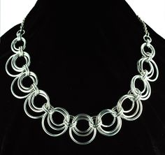 "Three sizes of rings nestle next to one another, creating a scallop shape. Light and airy, this necklace has a lot of motion. It looks great over a solid-color sweater, or with a plunging neckline shirt. Aluminum with rhodium-finish chain. Approx 18"" long."
