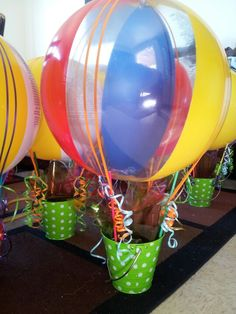 DIY Air Balloon center pieces. I made this for my grandson's 1st birthday party he loved balloons! I weighed it down with a capri sun and stuffed with a bag of sour cream popcorn, and some lollipop's.  ★★No helium its a beach ball, yes on the sticks there dowels I hot glued them to the inside of the bucket and the part of the beach ball that you blow I tied the curling ribbons to anchor the ball to dowels and used a dab of hot glue to stop the ribbons from crawling. ●◆■♥