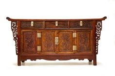 """CHINESE HUANGHUALI ALTAR COFFER.   Late 19th - early 20th century. Finely figured wood. Three dovetailed drawers with locking hardware over two folding doors, all with relief carving of birds and prunus branches. Pierce carved decorative panels. Fine condition with few minor pieced restorations. 36""""h. 72""""w. 17.5""""w.    From the collection of the late Honorable Richard P. Butrick, a career diplomat who spent twenty years in China during the early 20th century.  Estimate $20,000-40,000…"""