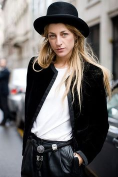 Ada Kokosar, in leather trousers, hat, white t-shirt.