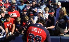 Atlanta Braves closing pitcher Jason Grilli (39) signs autographs for fans before the start of a baseball game against the New York Mets, Saturday, April 11, 2015, in Atlanta. (AP Photo/John Amis)