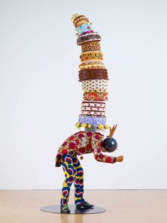 Cake Man (2013) Life-size mannequin, Dutch wax African-printed cotton textie (Kente cloth), leather, gold, polyester, and plaster