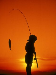 Silhouette of Boy Fishing at Sunset Photographic Print
