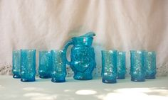 1960's Anchor Hocking Rain Flower Glass Set  This stunning Rain Flower Pattern by Anchor Hocking is a complete 9 piece set. The color is known as Ice Lip Laser Blue.   This set is in FLAWLESS vintage condition. The pitcher includes the Anchor Hocking mark on the bottom of the glass.