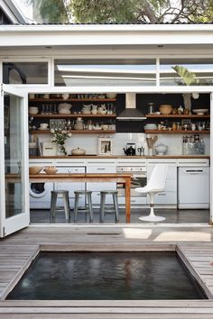 The kitchen in the home of Warren Matthee and Rupert Smith, owners of Cape Town decor stores O.live (olivestudio.co.za), opens into the courtyard and plunge pool.