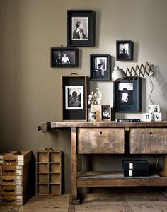 Foto's krijgen een stoere, nonchalante uitstraling door ze in houten kistjes, oude lades of houten deksels met een grote spijker – dwars door de foto en het hout – aan de muur op te hangen.