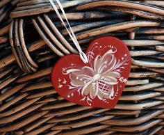 Rosemaling designs. Here white painting on small red flat heart.