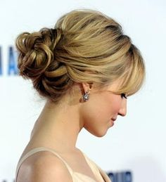 Simple curled low-do bun with side swept bangs.