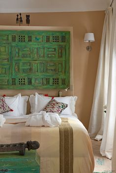 Riad Anata Fès Maroc Moroccan bedroom with carved wood headboard painted green