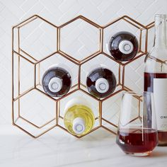 Geometric wine rack creates a coppery hive for 11 wine bottles. Crafted of slim iron rods hand welded into place, the rack lends a contemporary artful presence to the kitchen countertop, wine cabinet or bar. Versatile rack may be positioned vertically or horizontally.