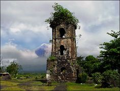 """Cagsaua ruins and Mayon Volcano - The ruins of Cagsaua Church along with the perfect cone of Mount Mayon rising up behind is one of the most famous tourist attractions in the Philippines. The church in front was partly buried in volcanic ash during the eruption of 1814. Historical Plaque, placed by the Philippines Historical Society in 1954, provides the history of the location."""