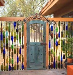DIY Wine Bottle Wall Fence. Beautiful backyard garden inspiration for your home! Creative gates for a gorgeous entryway into a yard or flower garden. Lovely tour of homes. LivingLocurto.com #backyardgarden