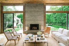 The double-sided, board-formed concrete fireplace, designed by architect Jeffrey Allsbrook, is the focal point of the living room. Kayne and Ehrlich lowered the ceilings by a few feet to make the space feel more intimate. Reclaimed wood beams and planks on the ceiling were salvaged from a Pennsylvania barn; woven leather and carved wood chairs from JF Chen; custom Molly Isaacson white linen sofas.