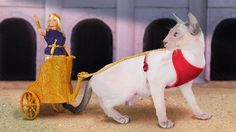 Cat pulling Romanesque Barbie in a 3d printed chariot     Fair Play 2: When In Rome by Jim Rodda/Zheng3