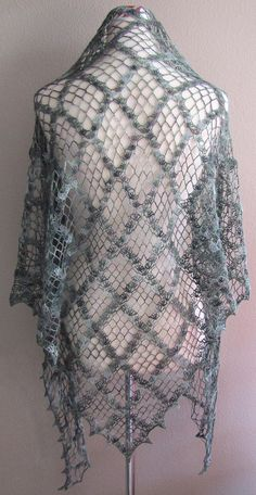 This is a beautiful handmade lace crocheted shawl made from a 70% baby alpaca 30% silk blend yarn. Pattern is done with lovely chained/netted squares and shells with a pointed shelled edging. Yarn is varied colors ranging from dark green, regular green, light green, and brown. Basically