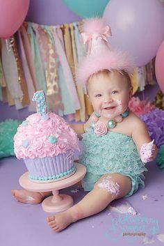 Cloth strip background   Purple bottom cake matches background Beading on cake matches romper