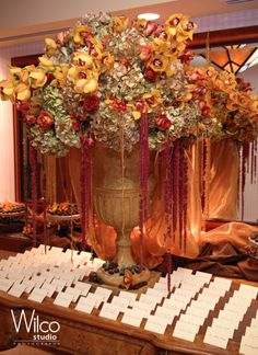 Placecard table with a gorgeous floral arrangement, dressed with chocolates on the bottom. #chocolatefactory #linzievents #chocolatetheme