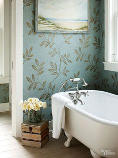 Footed tubs benefit from backdrops that highlight their striking silhouettes. In this beach house bathroom, a pretty wallpapered alcove trimmed in crisp-white woodwork provides an elegant setting for a tub supported by Victorian-style ball-and-claw feet. Although newly made, the tub filler and hand shower sport a vintage feel thanks to porcelain details and cross handles./