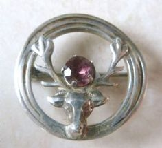 Vintage, Scottish, sterling silver stag with faux amethyst stone brooch manufactured by WBS, Ward Brothers. The dainty brooch has a stags head, set within a circle, to the center of the stags antlers is set a faux amethyst gem stone.