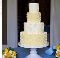 Ashley and Allen's elegant, white and yellow buttercream-frosted wedding cake was one of the bride's favorite parts of the day. Two of the four tiers were decorated with tiny flowers, and the others featured a fun swirl pattern.