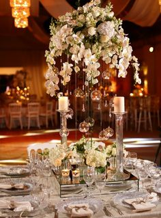 white wedding centerpieces in orchids, hydrangeas, roses and snapdragons with hanging crystal balls