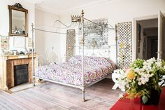 Colorful bedding in Parisian bedroom with canopy bed and fireplace